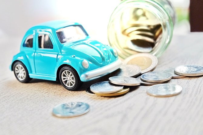 Blue car toy over a jar of coins