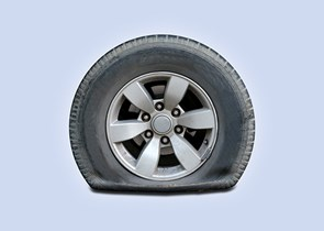 Wheel with a flat tyre on a blue background