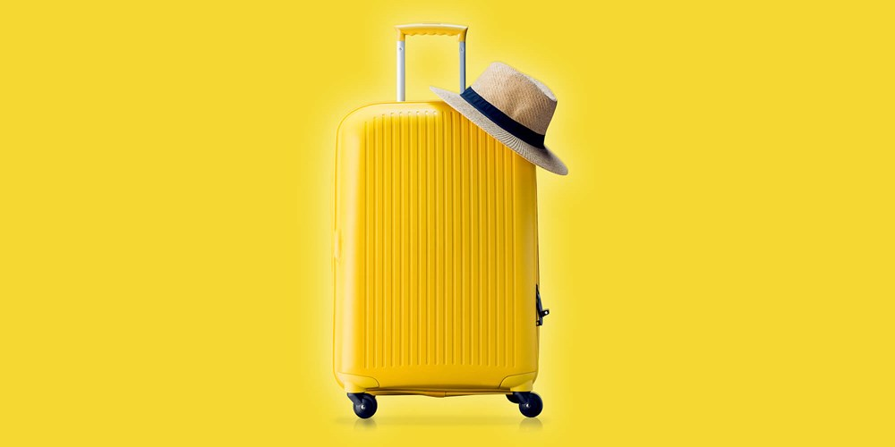 Yellow suitcase and a hat