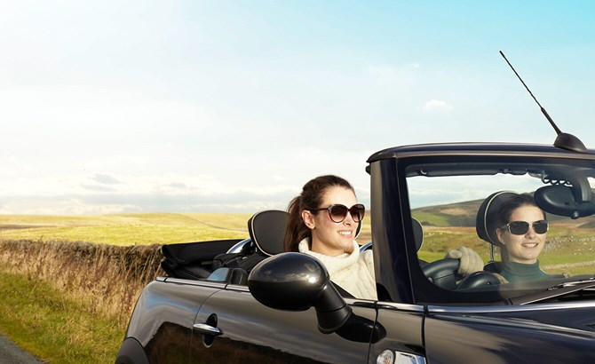 Two young women in a convertible smiling