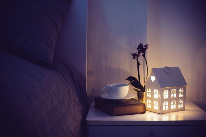 A bed side table with a light and a book