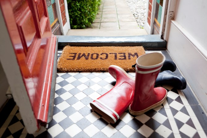 A welcome door mat by an open door next to a pair of red wellies