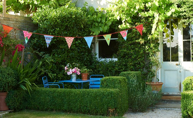 A garden with table and chairs and bunting above