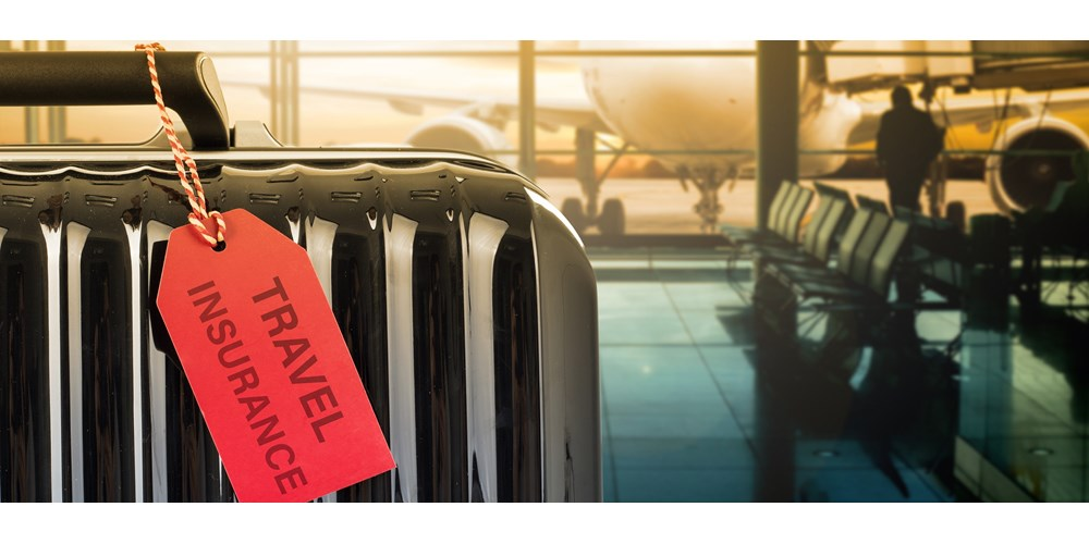 Black suitcase in an airport with a red travel insurance tag