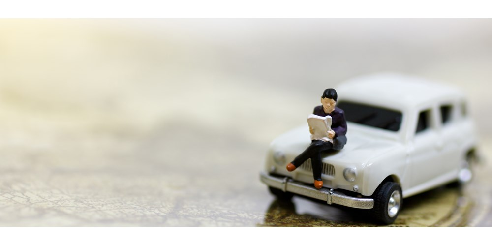 Toy white car and man sitting on bonnet