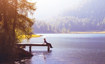 A woman sat at the side of a lake