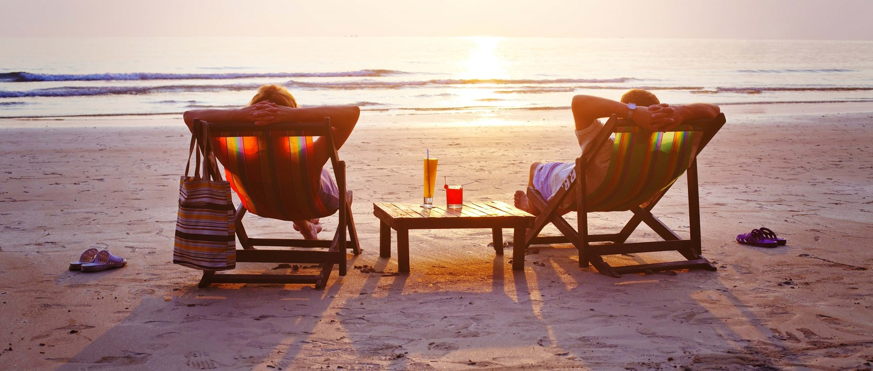 A couple sat on deck chairs on the beach