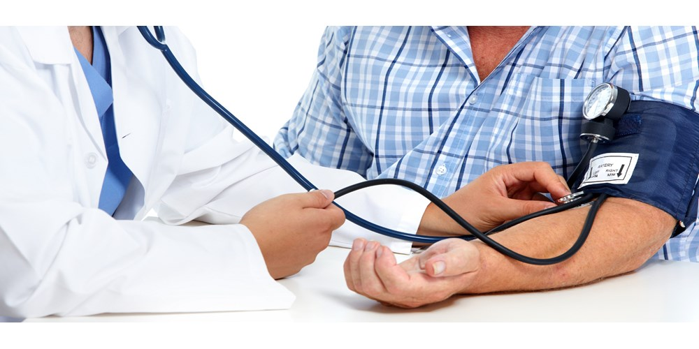 doctor checking male patients blood pressure
