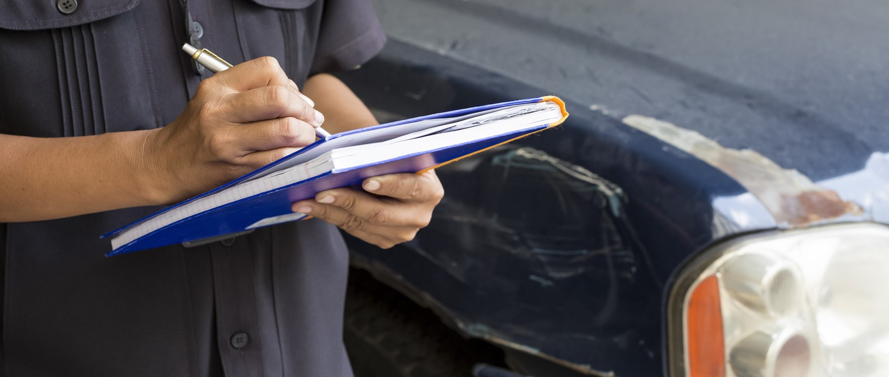 Man filling out form next to a damaged car