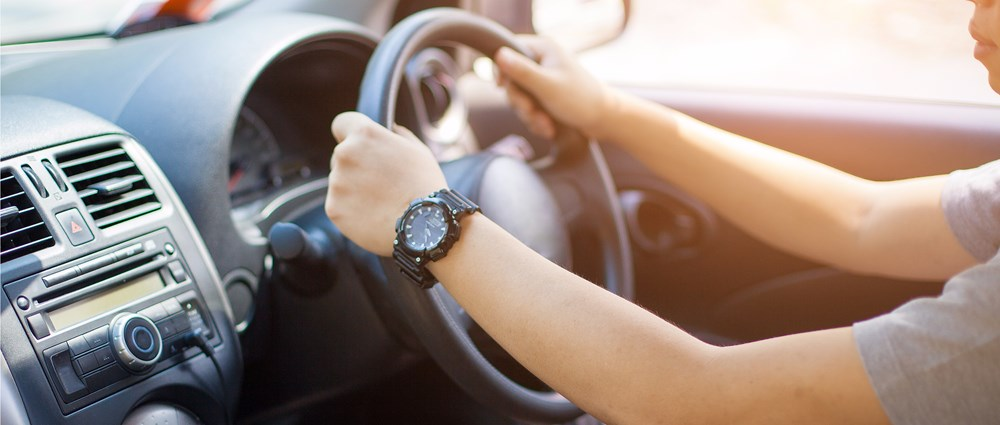 Hands on the wheel of a car