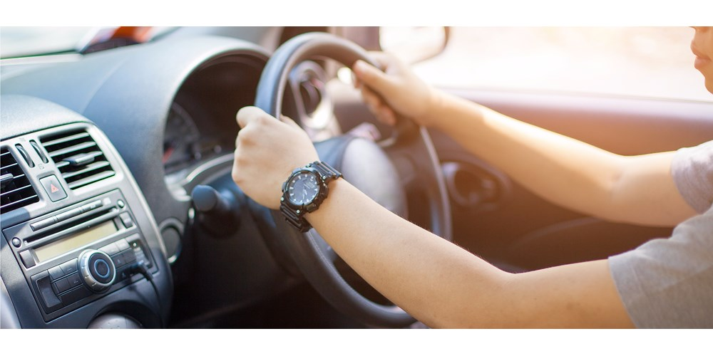 Woman's hands on the wheel of a car