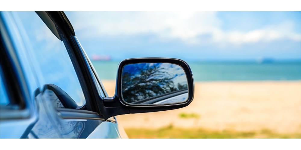 The wing mirror of a car parked at the beach