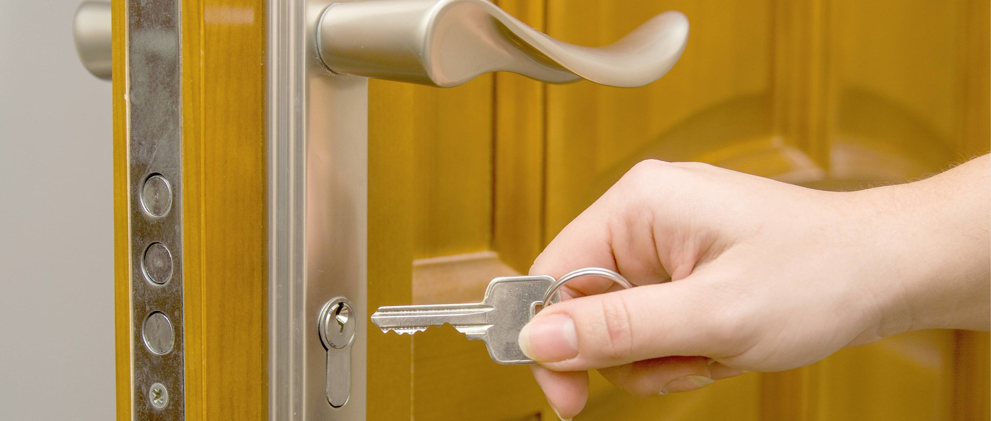 Someone unlocking a door with a key