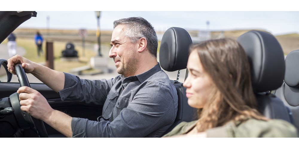 Man in his fifties driving convertible with teenage daughter