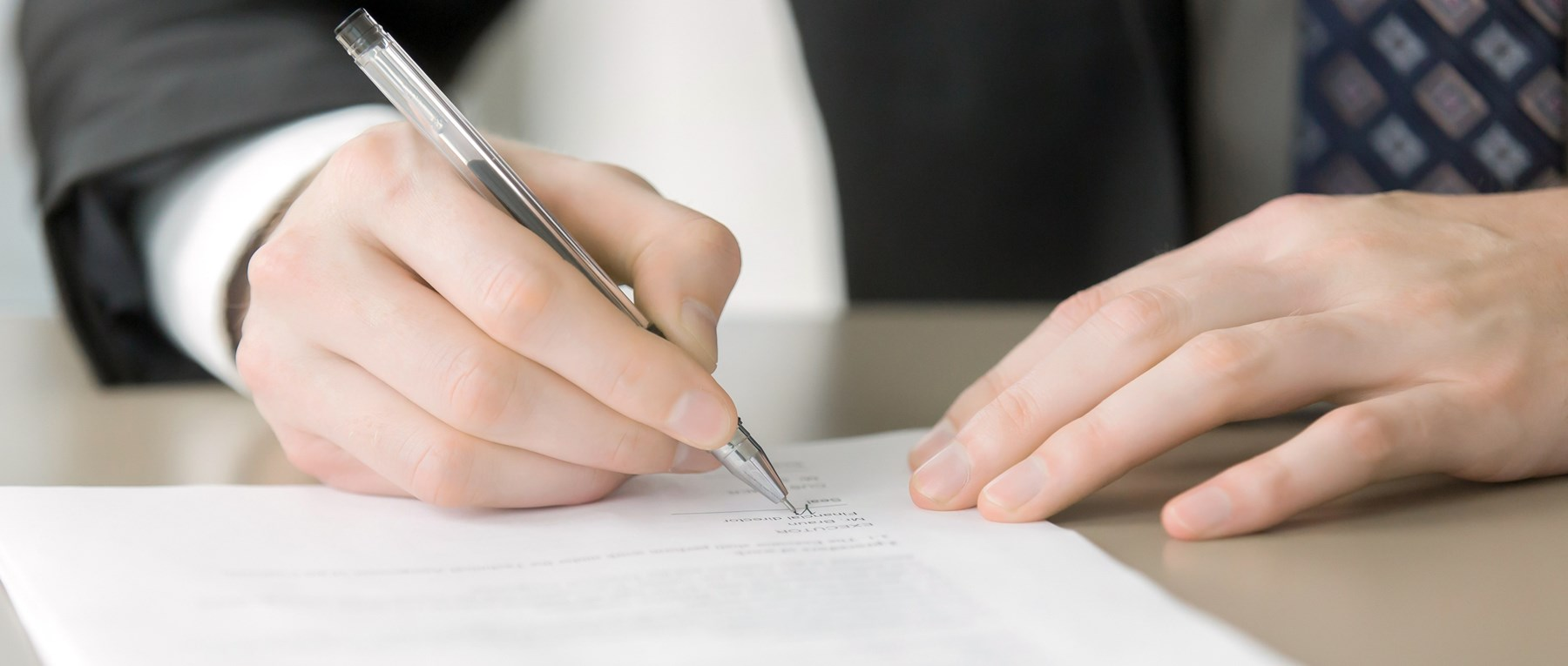Man in a suit signing document