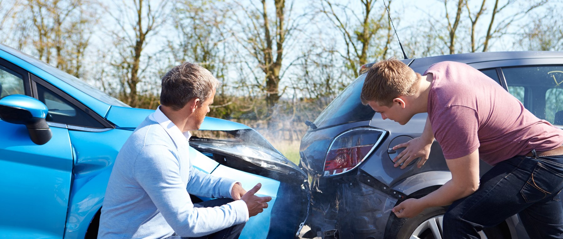 Two men looking at cars after collision
