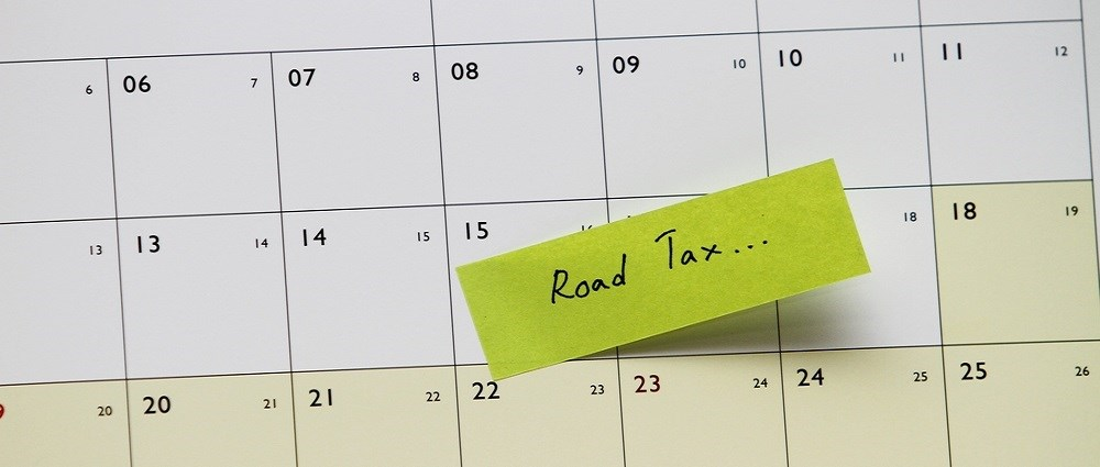 "A calendar with a post it note saying ""road tax"" on one of the dates as a reminder"