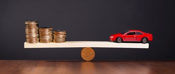 Toy car and coins on a scale