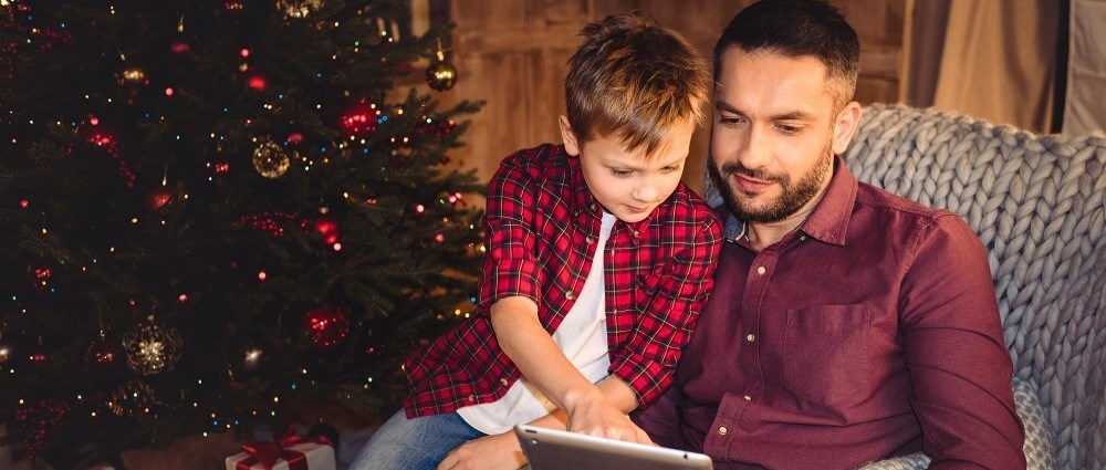 Father and son with tablet by Christmas tree