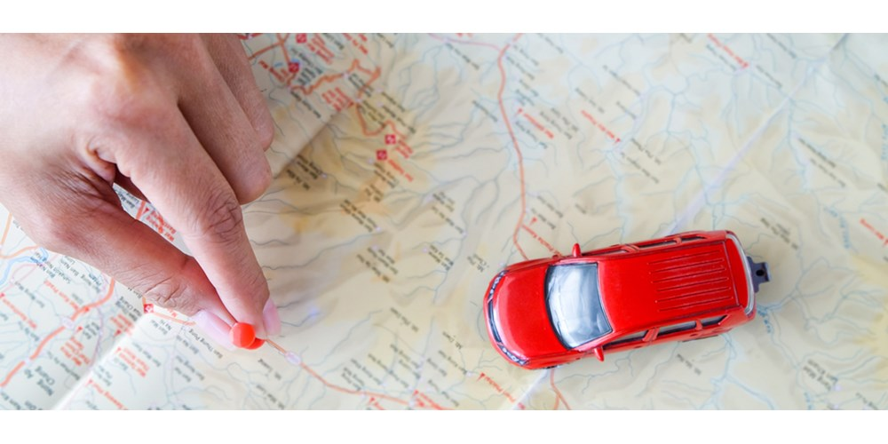 hand pinpointing location on a map with a toy car
