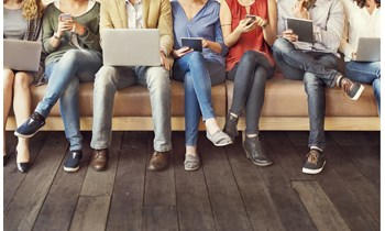 People sat in a row looking at laptops, tablets and phones