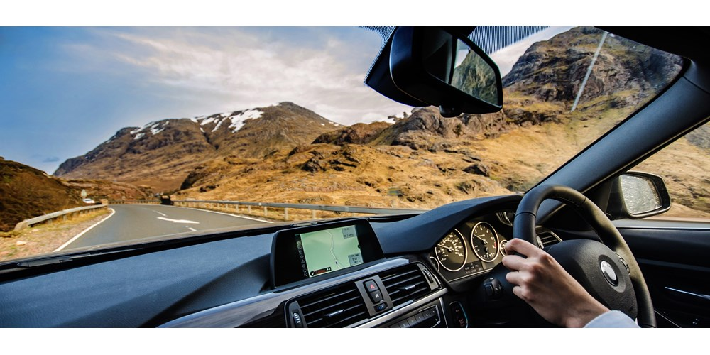 Man driving a car on a scenic road