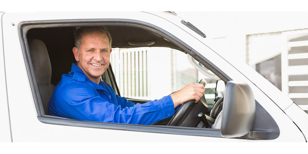 Smiling man driving a white van