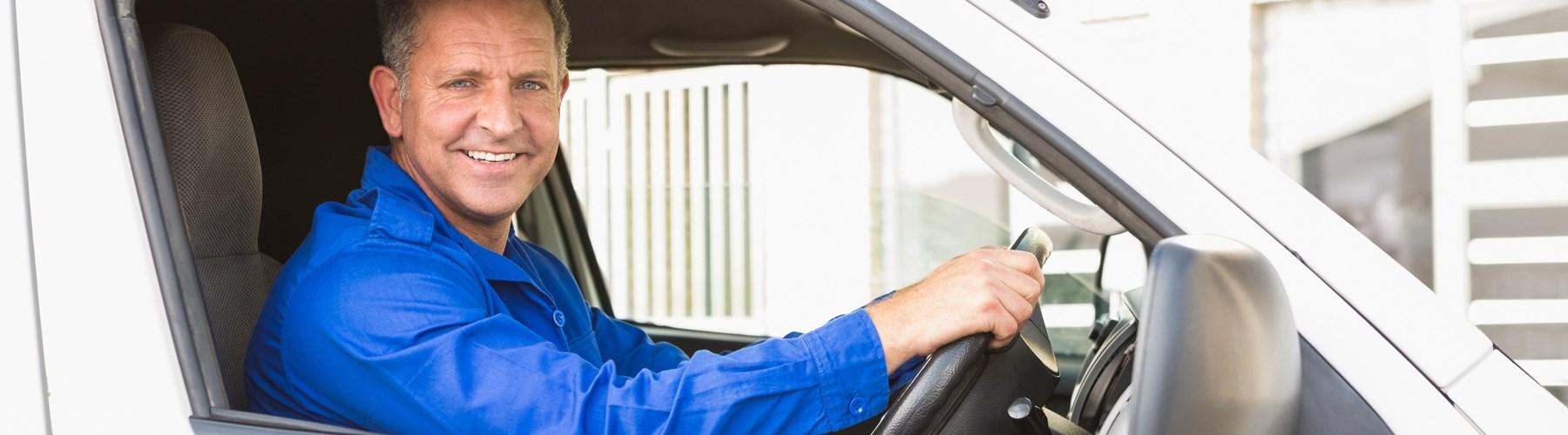Smiling man driving a white van