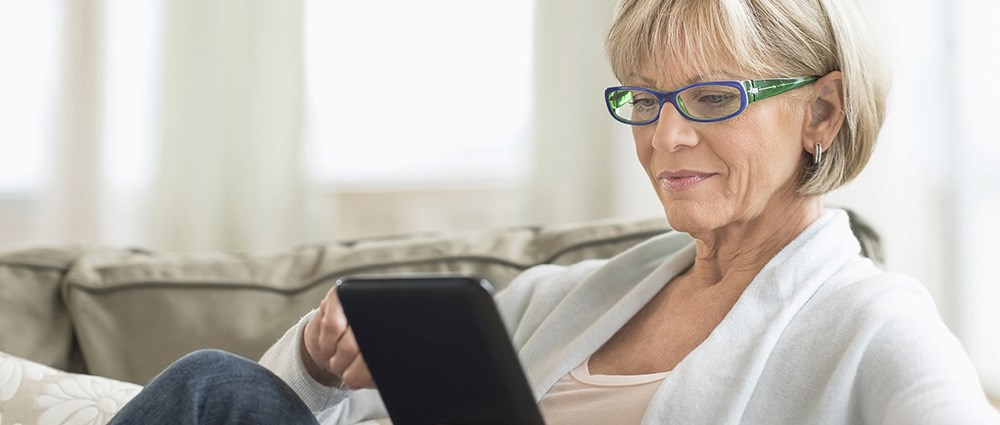 Woman playing on her ipad on the sofa
