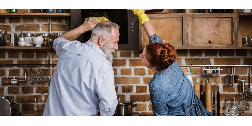 Couple cleaning kitchen