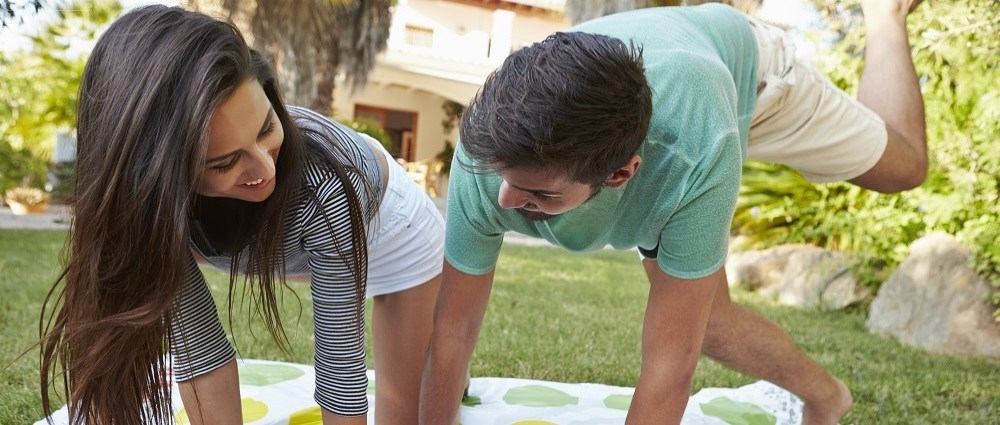 Woman and man playing twister in the garden