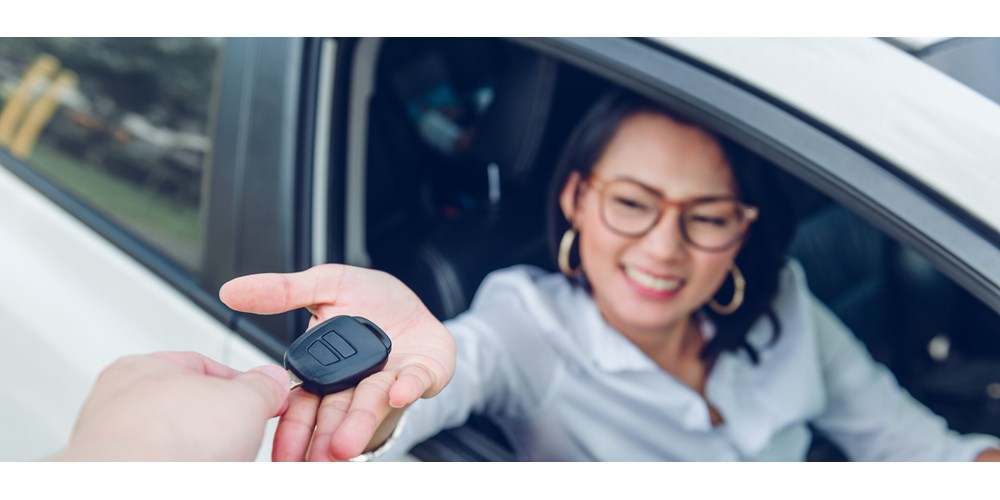 Young woman in car receiving car key