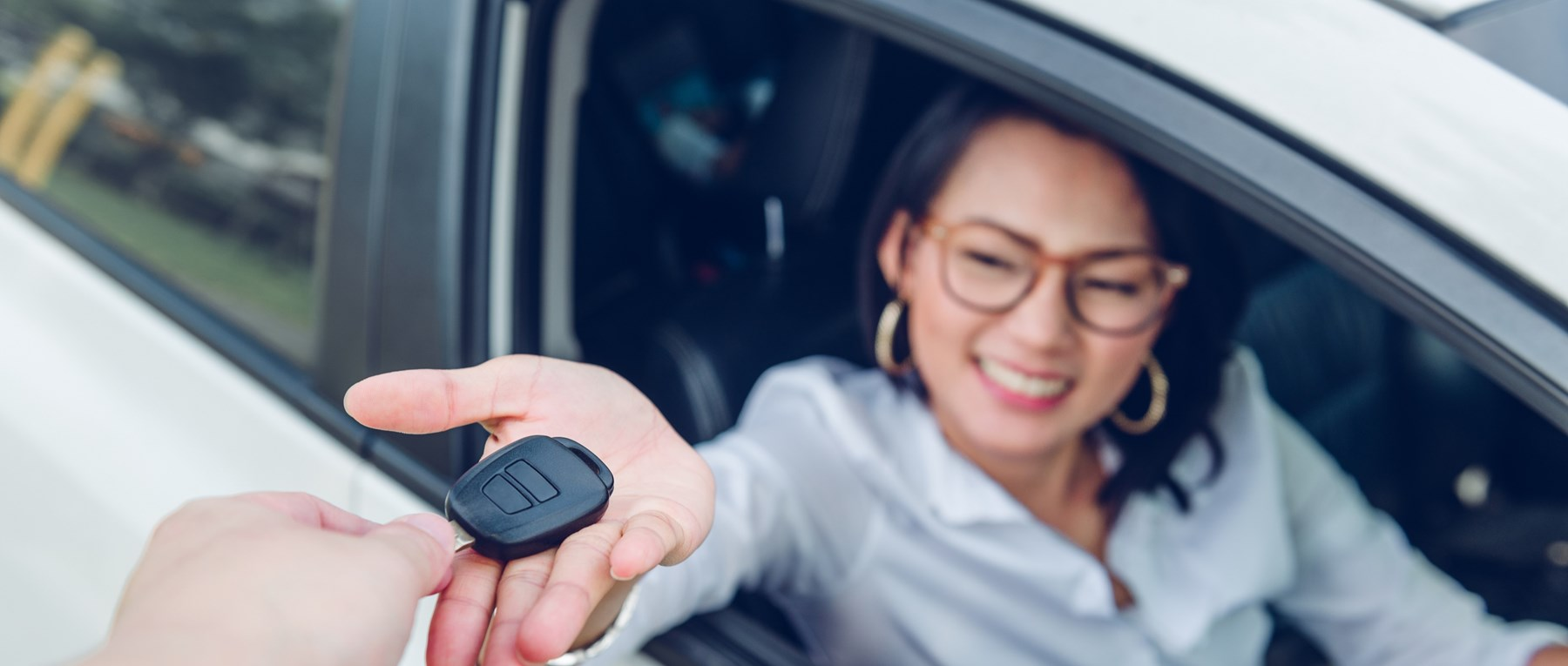 Young woman in car getting car key