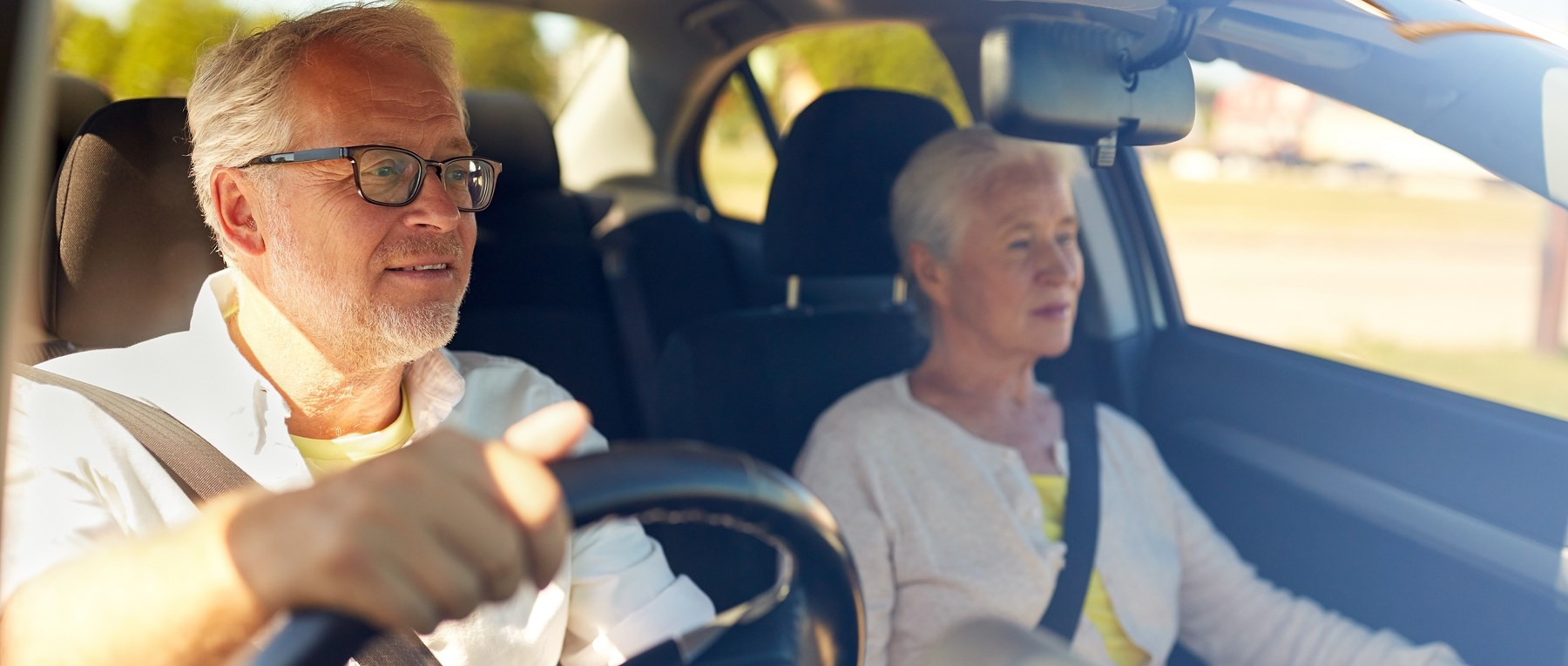 Older couple in car with male driver wearing glasses