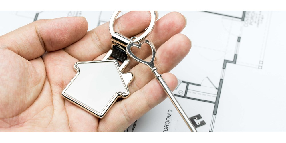 Hand holding a silver key with a house key ring