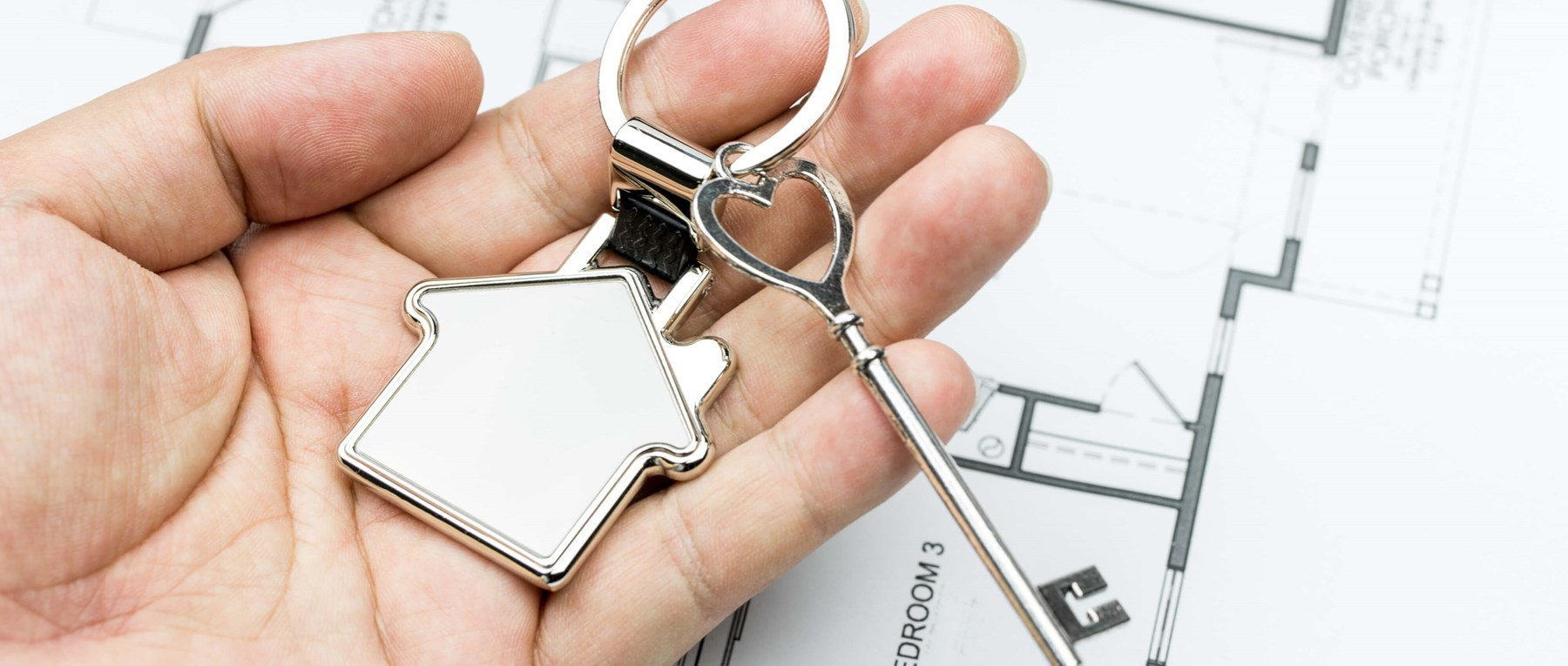 A silver key with a house key ring