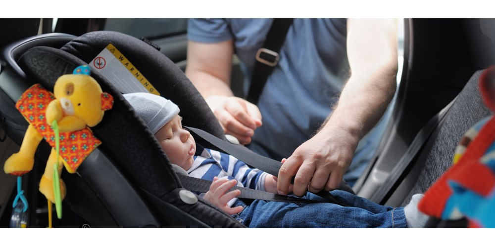 Baby being fastened in child car seat