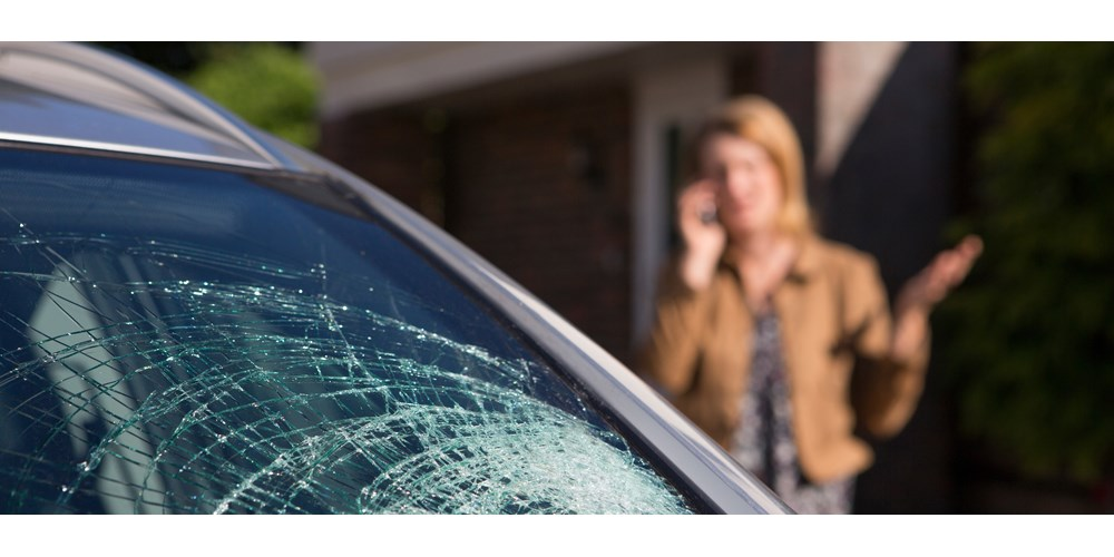 Broken car windscreen and woman on the phone