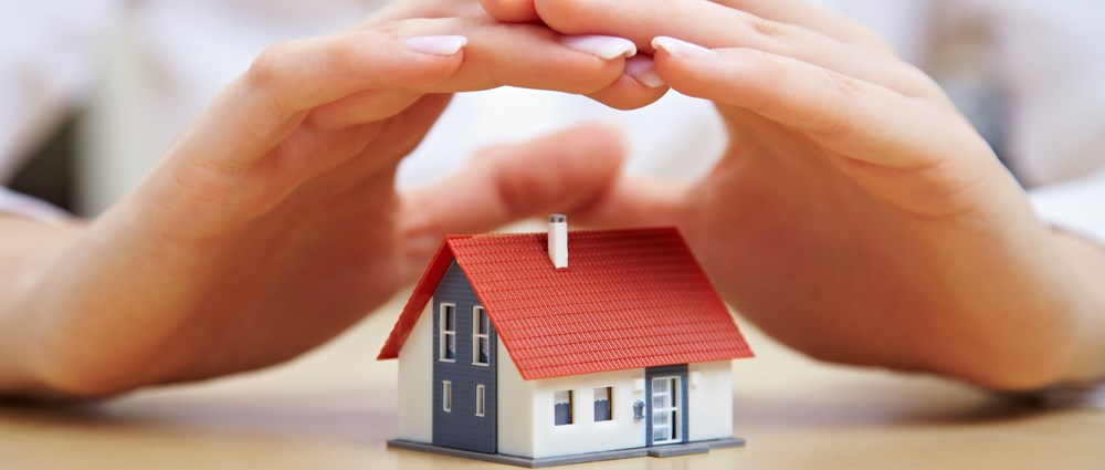 Woman's hand protecting a house