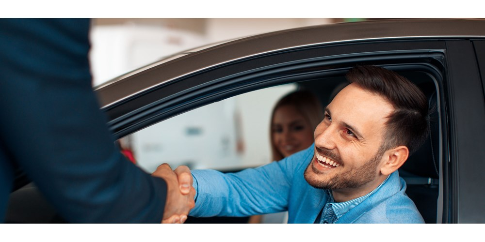 man shaking on buying a used car