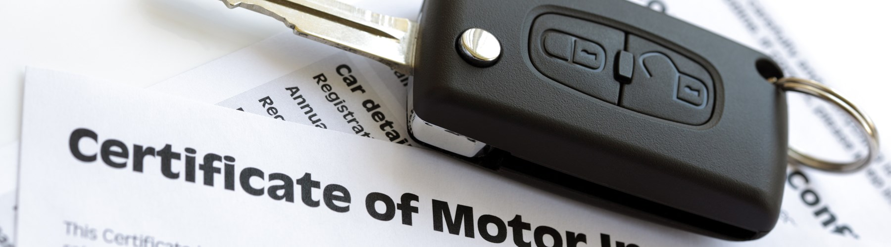 Car key on certificate of motor insurance