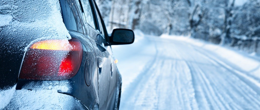 Woman scraping car windscreen on snowy day