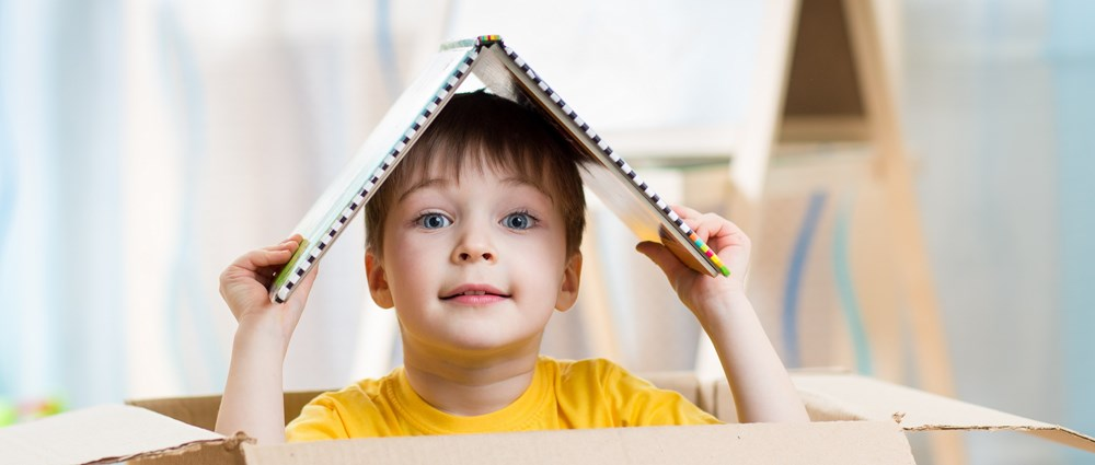 Child playing in box at home