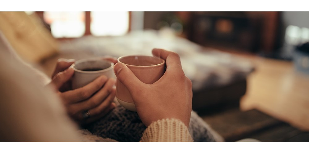 Couple holding mugs in front of fireplace