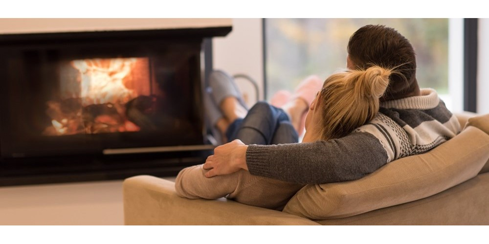 Couple sitting on sofa in front of fire