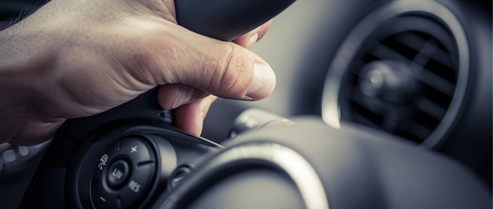 A man's hand on a steering wheel