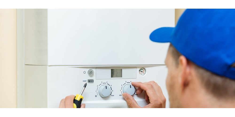 Engineer with blue hat fixing boiler