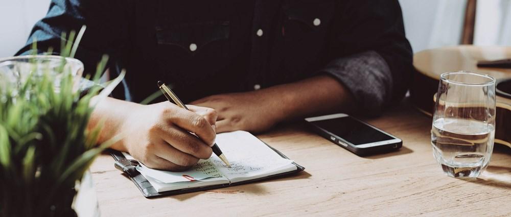 A man sat at a desk writing a list