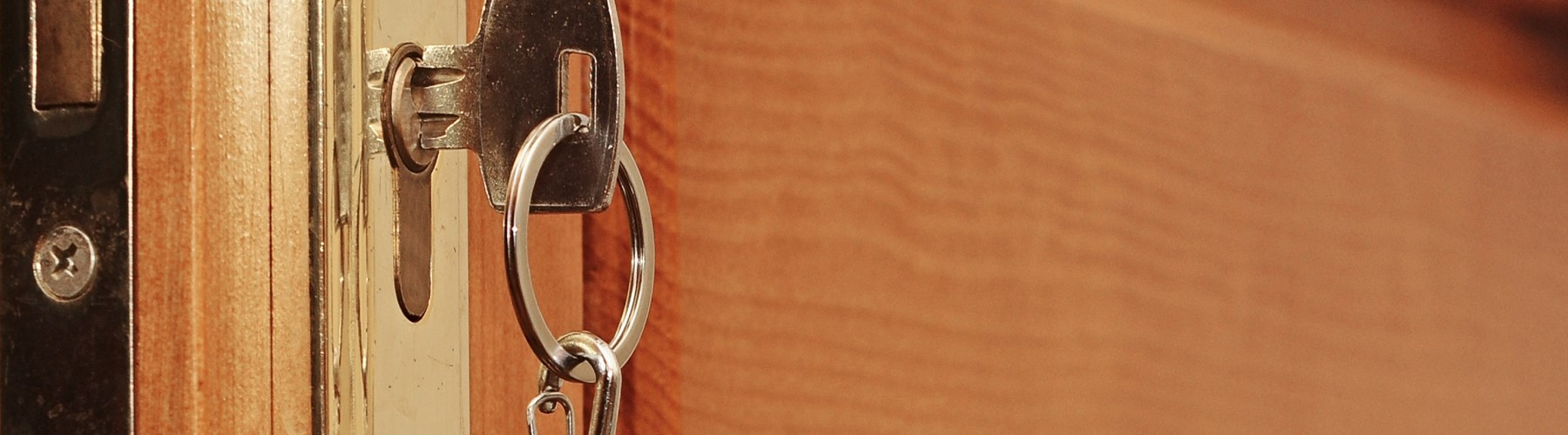 A wooden door being locked with silver key