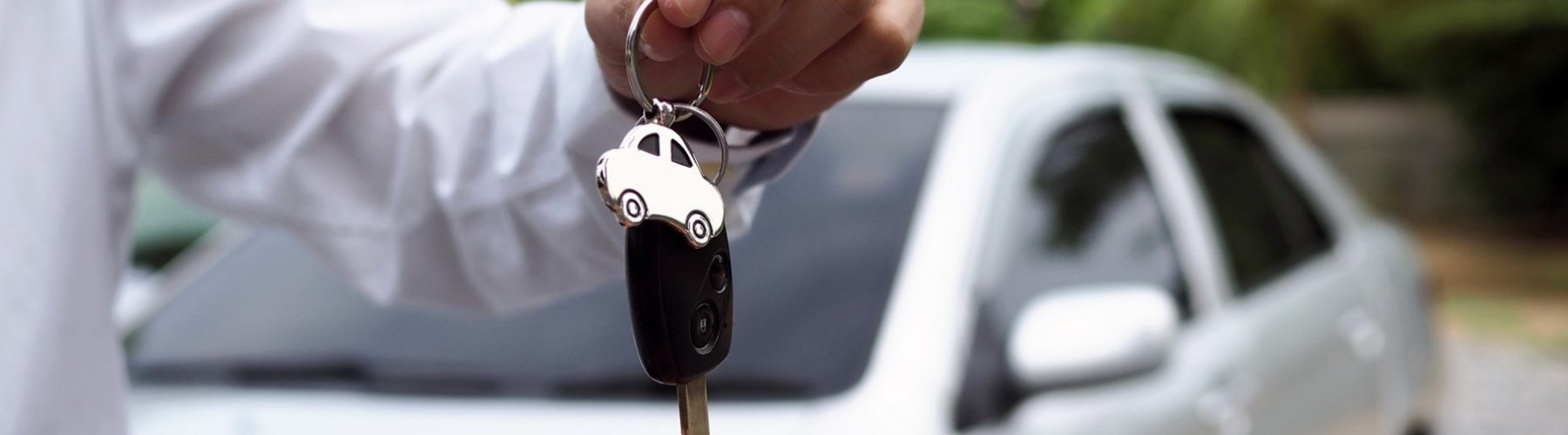 Man handing over car keys in front of silver car